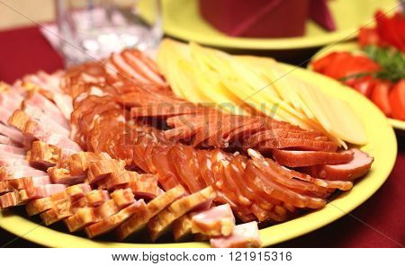 Slices of sausage, bacon and cheese on plate