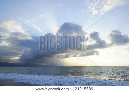 Sun ray clouds is lit brightly light golden seascape with waves rolling to the shore as scattered sunbeam break through a dramatically onto the ocean horizon.