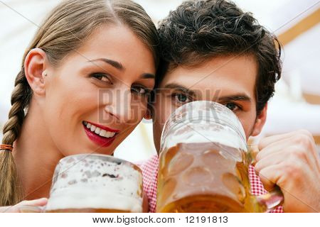 Couple in traditional German costume in a beer tent having a drink