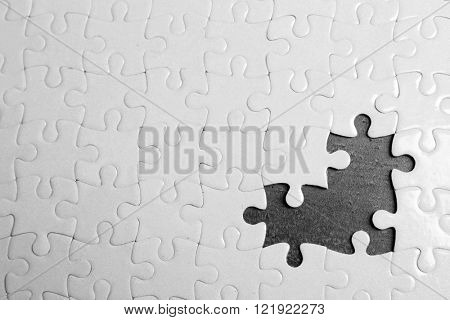 White jigsaw puzzle with missing pieces on grey background
