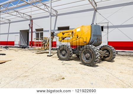 Cherry picker parked next to a newly painted metal frame building.