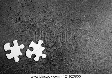 Two pieces of white jigsaw puzzle on grey background