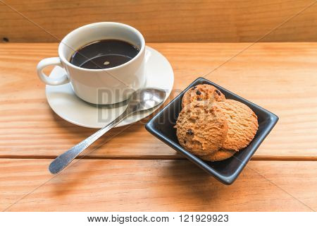 Chocolate chips cookies with white cup of coffee focus at chocolate chips cookies