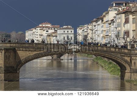 FLORENCE ITALY - MARCH 07: Ponte Santa Trinita bridge over the Arno River shown on March 07 2016 in Florence Italy. The Ponte Santa Trinita is the oldest elliptic arch bridge in the world