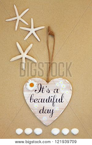 Its a beautiful day distressed wooden sign with starfish and cockle shells on beach sand background.