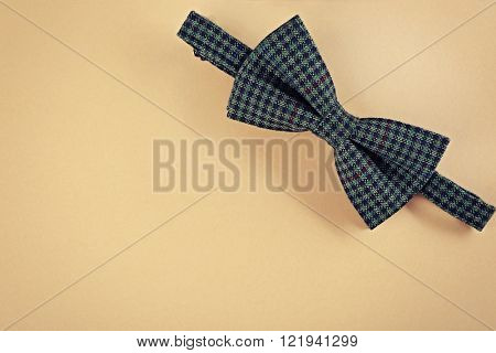 Green bow tie on beige background