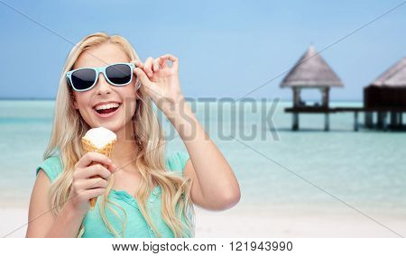 summer vacation, travel, tourism, junk food and people concept - young woman or teenage girl in sunglasses eating ice cream over beach on touristic resort background