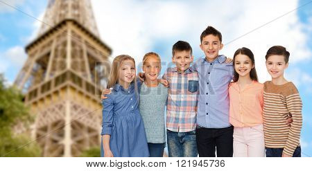 childhood, travel, tourism, friendship and people concept - happy smiling children hugging over paris eiffel tower background