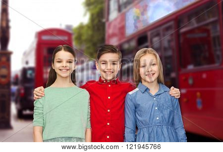 childhood, travel, tourism, friendship and people concept - happy smiling boy and girls hugging over london city street background
