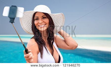 lifestyle, leisure, summer, technology and people concept - smiling young woman or teenage girl in sun hat taking picture with smartphone on selfie stick over beach and swimming pool background