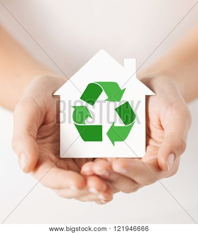people, ecology, environment and conservation concept - close up of hands holding house with green recycling sign