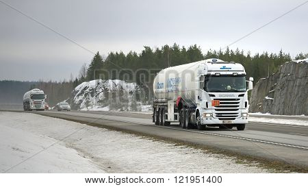 PAIMIO, FINLAND - MARCH 12, 2016: Two Scania semi tank trucks in ADR haul along motorway. The ADR code 223 1972 signifies methane refrigerated liquid or natural gas with high methane content.