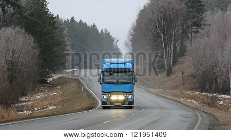 SALO FINLAND - MARCH 13 2016: Blue Renault Trucks T Semi drives along road in winter landscape. The driver flashes the headlights briefly.