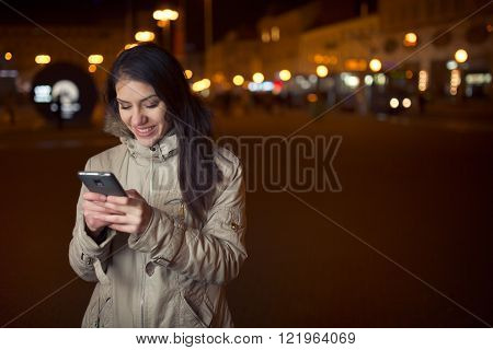 Euphoric woman using her smart phone and smiling to good news message.Happy woman typing text message on a smart phone on a city street.Communication with people,distant relationship connections