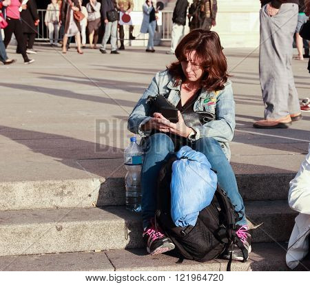 Woman sitting on the stairs reading a message on your mobile phone