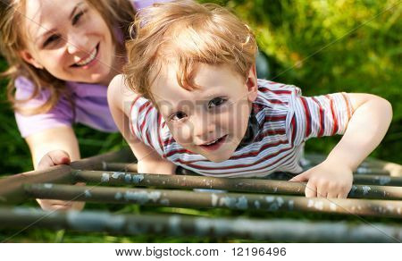 Little boy and his mother climbing up a ladder from a meadow, they want to reach their tree house (house not to be seen)