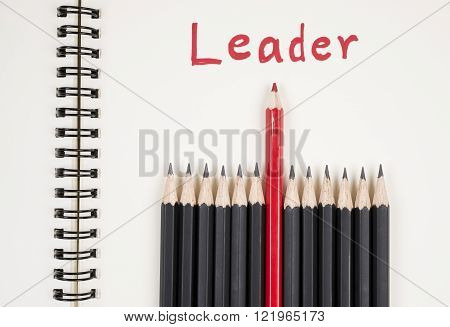 Red pencil standout from black pencil and handwriting word Leader on wood background leadership business concept poster