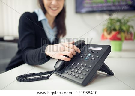 Young business woman answering phone call.Good news.Customer service representative on the phone.Cheerful secretary answering phone in her office.Desk table office phone and woman hand picking up