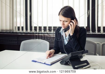 Worried stressed office worker business woman receiving bad news phone call.Looking confused checking notes and paperwork.Manager solving mistake.Disputes,problems,Complaint,grievances at work. poster