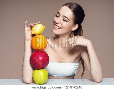 Healthy & Happy natural organic raw fresh mix fruits concept / portrait of girl with fruits mix on the table over beige backdrop