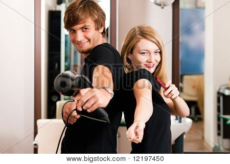 Two hairdresser - man and woman - posing for the camera in the hairdresser's shop