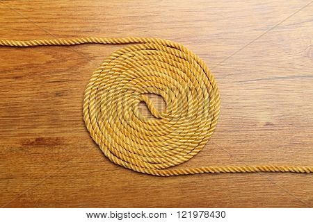 Ball of hemp rope on wooden plate. Industrial background.