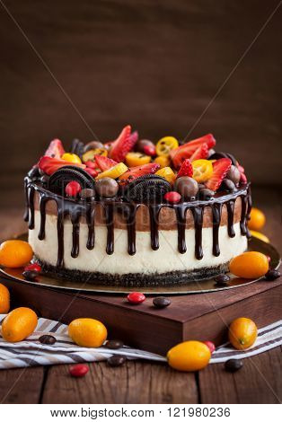 Two-ply chocolate cheesecake decorated with fresh strawberry kumquat and chocolate
