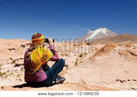 South America - The surreal landscape in the Eduardo Avaroa National Reserve of Andean Fauna near Chilean border. The woman will look through binoculars on the mountain poster