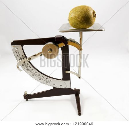 Old letter scale with a kiwi fruit on.