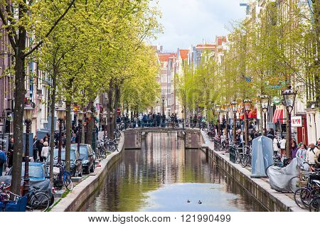 Amsterdam-April 30: Amsterdam  Red Light District full of tourists on April 30 2015 the Netherlands. The Amsterdam Red Light District is one of the most iconic places in all of Europe famous for its liberal laws cafes and ladies of the night.