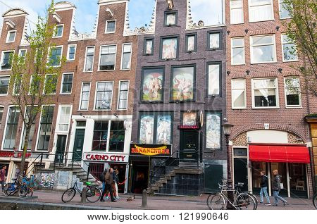 Amsterdam-April 30: Red Light District tourists go sightseeing on April 302015 the Netherlands. The Amsterdam Red Light District is one of the most iconic places in all of Europe famous for its liberal laws cafes and ladies of the night.