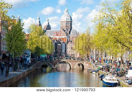 Amsterdam - April 30: Red light district crowd of tourists go sightseeing the Church of St. Nicholas is visible in the distance on April 30 2015 the Netherlands.