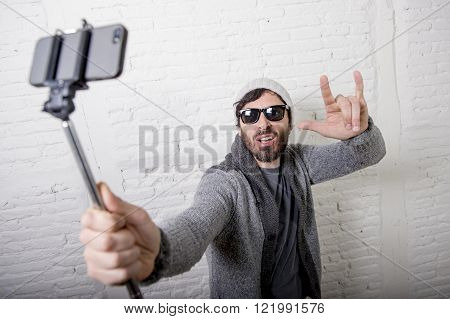 young attractive man in casual clothes beanie hipster style holding selfie stick mobile phone shooting self portrait photo or recording video in internet blog and blogger concept