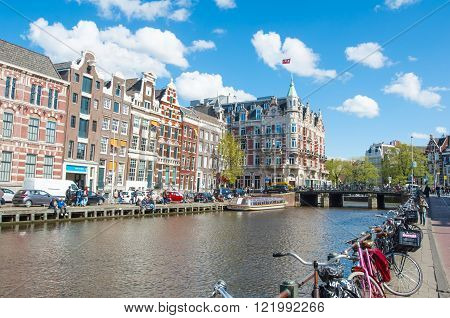 Amsterdam-April 30: Rokin canal with bikes parked along the bank Hotel de l'Europe is visible on the left tourists enjoy cityscape on the opposite side on April 30 2015 the Netherlands.