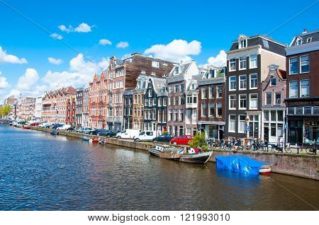 AMSTERDAM-APRIL 30: Amsterdam cityscape with row of cars bikes and boats parked along the Singel canal on April 30 2015 the Netherlands.