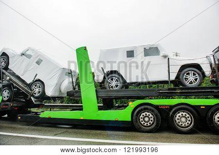 HUNGARY - SEPTEMBER 18, 2013: New luxury Mercedes-Benz G-Class SUV cars being transported on a HODLMAYR trailer near Hungarian border. Hodlmayr is an Austrian international transportation company