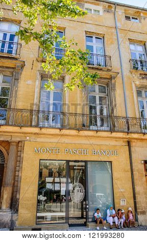 AIX-EN-PROVENCE FRANCE - JUL 17 2014: Arabic family on the steps of Provence headquarter of Monte Paschi Banque on the famous cours Mirabeau street. Banca Monte dei Paschi di Siena S.p.A. is the oldest surviving bank in the world and Italy's third largest