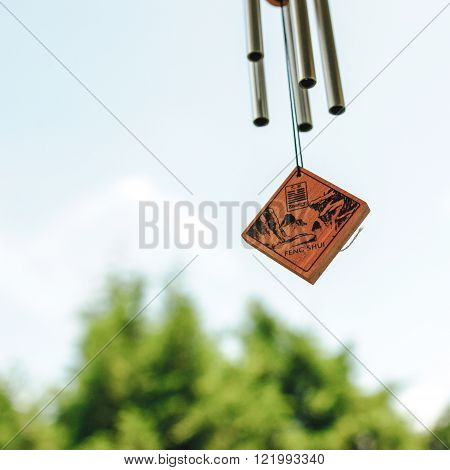 Feng shui chimes next to window with a clear blue sky and defocused tree in the background