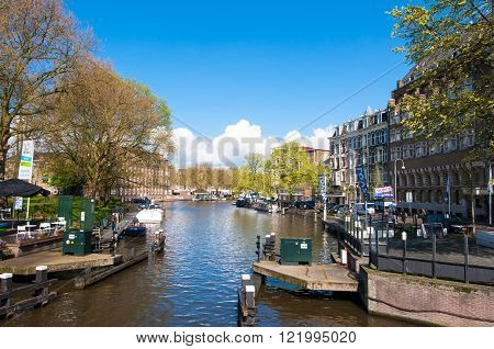 AMSTERDAM-APRIL 30: Singelgrachtkering Canal with boat station on the left hand side on April 302015 the Netherlands.
