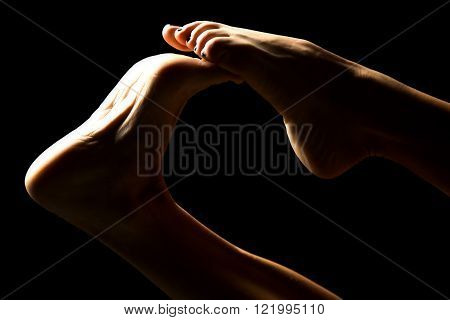 A close up of a woman's feet in the shadow playing with her toes.