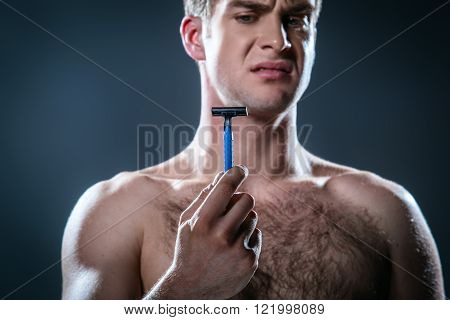 Studio portrait of handsome young man. Man with naked torso having skin irritation after shaving. Man holding disposable razor
