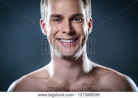 Studio portrait of handsome young man. Clean shaven man with naked torso looking at camera and smiling