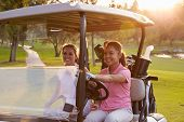 Female Golfers Driving Buggy Along Fairway Of Golf Course poster