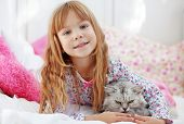 Portrait of child resting in bed with lovely pet poster