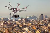 Drone flying in the sky against the backdrop of the beautiful cityscape. Copter is filming the photo of the urban landscape. RC Professional Travel drone poster