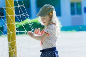 Nursery school girl is playing near football goal net with yellow goalposts poster