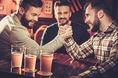 Cheerful old friends having fun arm wrestling each other in pub. poster