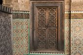 decorated wood door, tile work and carved calligraphy in the 14th century Bou Inania medrese in the ancient medina of Fes, Morocco poster