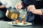 Chef pouring sauce on dish in restaurant kitchen, crop on hands, filtered image poster