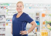 Female Pharmacist Standing With Hands On Hip In Pharmacy poster
